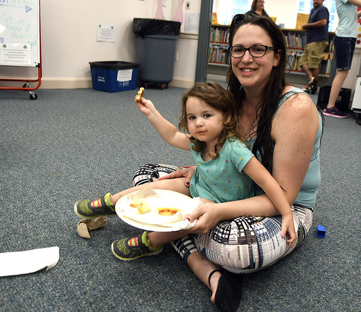 7/14/2017 Mike Orazzi | Staff Chris Carmody and her daughter Claire enjoy pizzza from California Pizza Kitchen at the Bristol Public Library Friday morning.