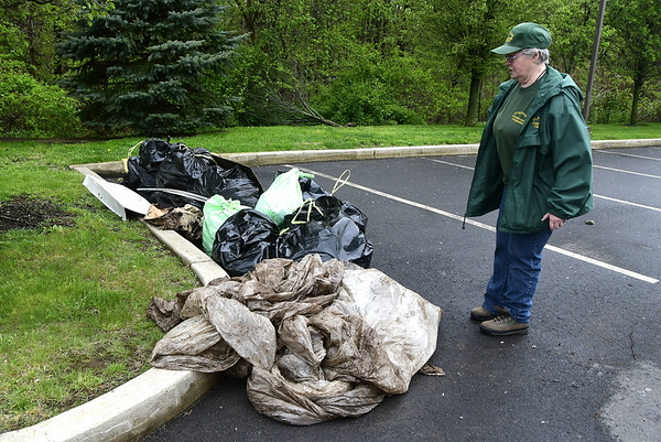 5/6/2017 Mike Orazzi | Staff Marge Burris walks past some of the trash collected along the Quinnipiac River during Saturday's clean up.