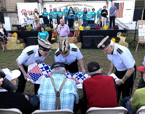 9/20/2019 Mike Orazzi | Staff Area veterans sign a quilt while being honored during the Mum Festival on Friday evening in Bristol.