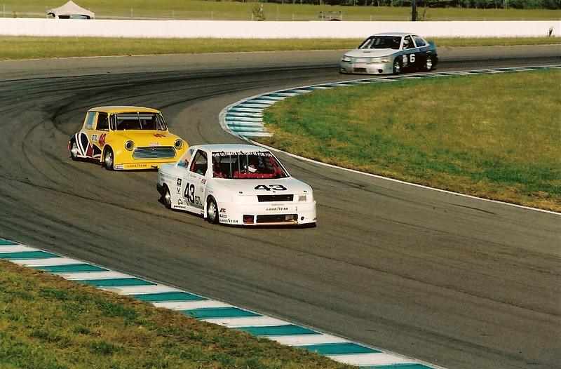 Accelerating out of turn eleven with Ted Phenix driving his Austin Mini Cooper followed by the NORPAC Division, Lans Stout driving his Nissan Sentra B14 Powered by a Rebello built Fuel Injected L16.