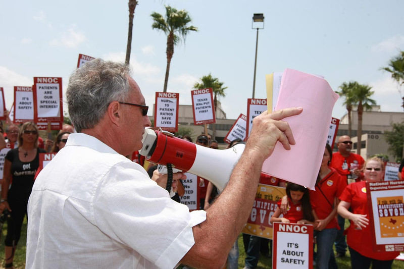 Ed Bruno addressing the crowd with a stack of documentation of unsafe practices at Valley Regional Medical Center