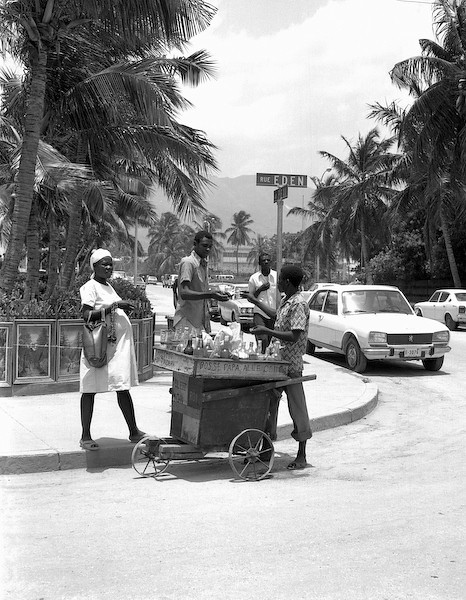 This image was selected by Buku to hang in their lobby.  It captures their theme of 'Global Street Food'.  It is a 30X40 inch photographic print, matted and framed to a 42X52 inches.<br /> <br /> 'Haitian Street Cart' was made in 1979 in Port au Prince, Haiti.  I used a Mamiya 6X7cm medium format camera and Tri-X black and white film. <br /> <br /> This was really quite a colorful photo in that the bottles in the cart contained a broad assortment of brightly colored liquids which, on this hot summer day, look quite refreshing (as represented by the queue).  I especially like the cart, basic but functional, made from scrap crates and lumber to transport this young man's means of earning an income.  It works particularly well as a black and white image because the distractions of the surroundings are quieted and your attention is first drawn to the main theme, the transaction of the street vendor and his customer, and then gradually released to explore more and more of the moment and the surroundings.