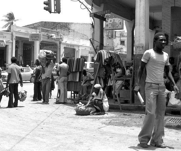 'Haitian Market Corner' was made in 1979 in Port au Prince, Haiti. I used a Mamiya 6X7cm camera and black and white film. The negative was scanned and the print was produced on AgX paper and processed.<br /> <br /> This photo was made in the fabric district of Port au Prince, but this busy corner has a broad range of activities, from people carrying their assorted wares hoping to be sold that day to people settled in the shade displaying their shoes, hats and fabrics.  The woman in the front center is selling cooked food rolled up in paper.