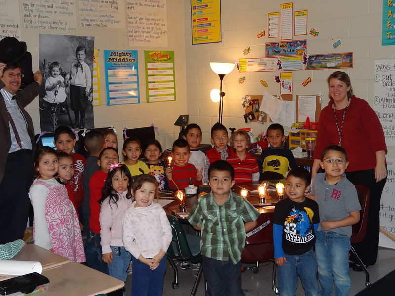 Ms. Farmer's first grade class standing with light bulbs.