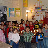 Ms. Farmer's first grade class standing with light bulbs.