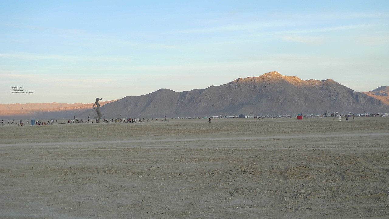 Bliss Dance towered over the playa, and the setting sun casts its last direct rays on the mountain tops in the background.