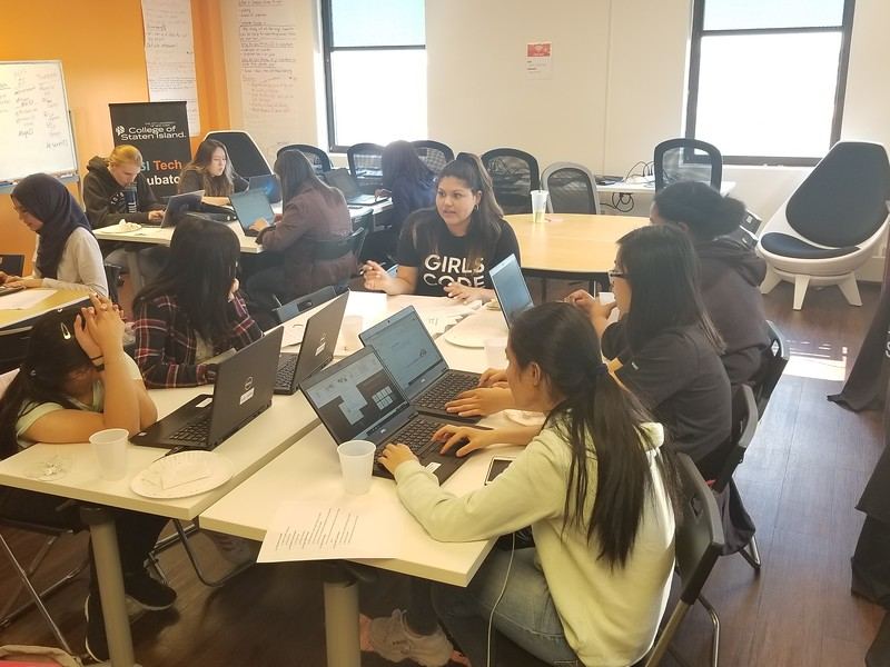 Kaylyn Torres (Club Facilitator) and students working on coding tutorials.