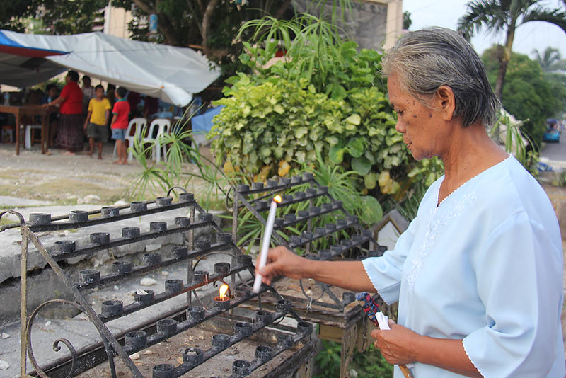 Parishoneers lighting a candle on what was left of the Church of Our Lady of Light here in Loon, Bohol. (Armie Garde)