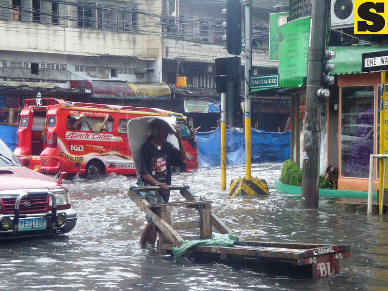 Man pushes cart amid heavy rains