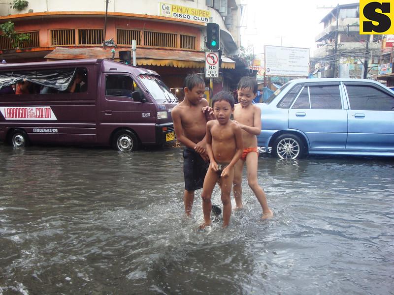 Boys taking a bath on flooded street