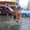Boys taking a bath on flooded street