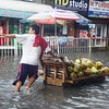 Vendor selling fresh coconut wades through flooded Sanciangko St. in Cebu City