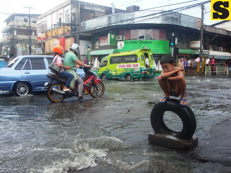 Boy on traffic warning device amid heavy rains