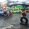 Boy on traffic warning device amid heavy rains