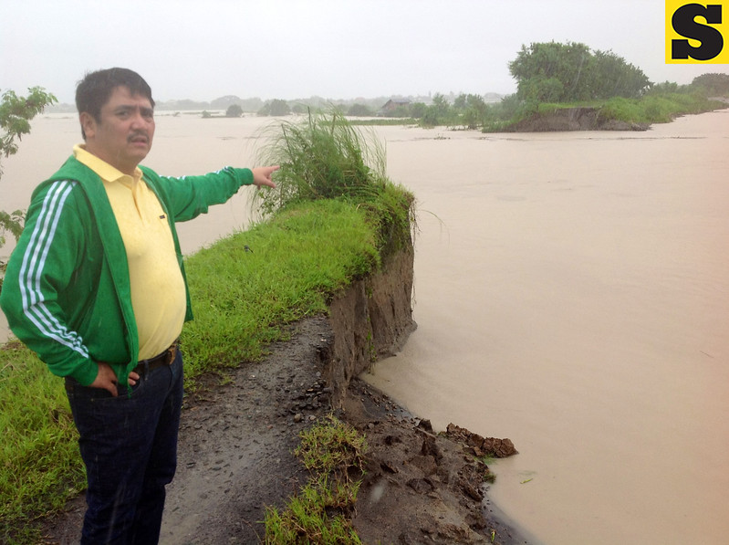 BREACHED DIKE. Rep. Dong Gonzales points to the portion of the tail dike that was breached by strong floodwaters on Wednesday. (Chris Navarro)