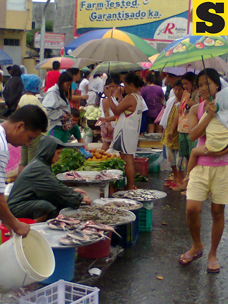 MAKESHIFT MARKET. Vendors settle themselves along the Gapan-San Fernando-Olongapo Road in Guagua town as the town proper remains inundated in floodwaters. (Ria de Fiesta)