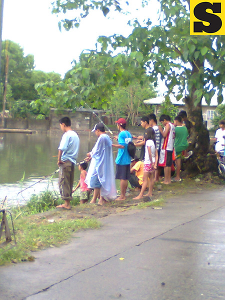 FISHING FOR FUN. After floods comes the fun, as this group of people try to catch either fish or frog along the GSO Road in Guagua town. (Ria de Fiesta)
