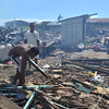 TACLOBAN. Residents clear debris and burn them at the back of the crumpled roofing materials on November 28 in Balangiga, Eastern Samar. (Gerwin Babon)