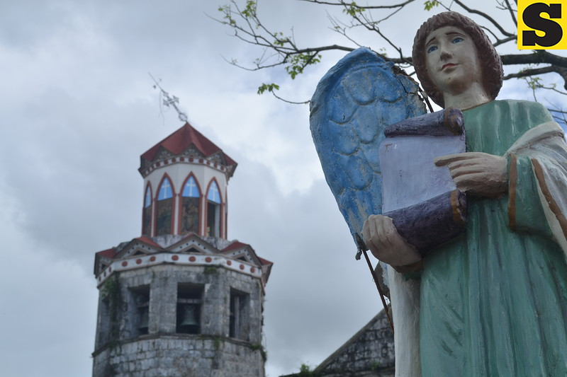 TACLOBAN. Statue of an angel with a broken wing with St. Michael's Church belfry at the background showing a leaning cross on top in Basey, Samar on November 28. The church structure remains intact, only the roof and some glasses were damaged by Yolanda. (Gerwin Babon)