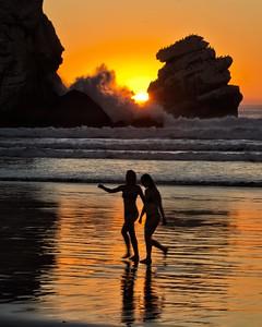 Waves crash on Morro Rock at sunset.