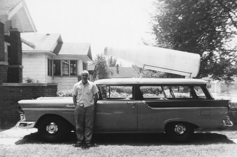 Chris Argus with Dad's Old Fashioned Root Beer Bottle. The car was new so this was in 1957. This was in front of our house in Hammond, In..