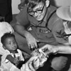 Naval Air Facility Sailors give orphanage children Christmas gifts in 1969. The orphanages are full of children of European extraction like the boy shown here. American genes are mixed with the local pool as they are in all wars. Among the Vietnamese such mixed children dishonor the mother, and the children are doomed to grow up in shame.