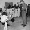 Christmas Day 1969 Naval Air Facility Commanding Office Henderson, starched, shinned and dapper,  takes officers and men to distribute Christmas presents at a local orphanage. The children sing and dance as GIs hide tears.