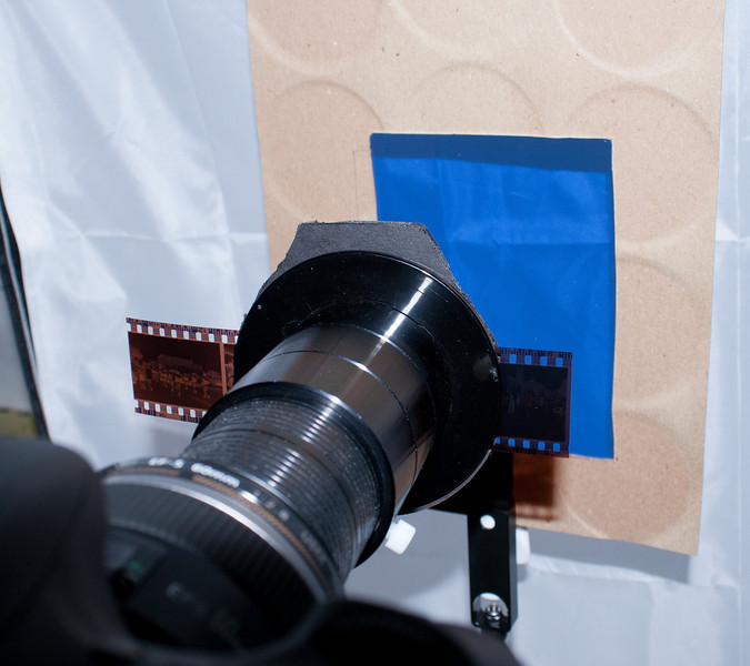 Carrier with negative mounted on PhotoSolve Extend-a-Slide.  Rosco #3202 tungsten-to-daylight filter is in between the carrier and the softbox (which isn't illuminated yet.)  The #3202 filter partially removes the orange mask.  VueScan converts better if the #3202 filter is used.    <br /> <br /> The tab on the front of the base plate is so I can clip another gel filter on, if I want to experiment with an additional layer of filter (from the Rosco Swatchbook of filter samples.)<br /> <br /> The softbox provides the diffusion, far away from the focus plane so that any dust that is on the front of the softbox diffuser will not be in focus.