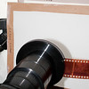 "Carrier mounted on Extend-a-Slide.  Illuminated by softbox with CFL lamps.  It is diffused by three layers of Rosco #3026 ""Tough White"" one stop diffusing material.  (The original plastic disk has about three stops of loss.)  A single layer on the frame that is closest to the softbox.  Two layers on the frame that is closest to the Extend-a-Slide.  Position the two stop diffuser so it is as close to the Extend-a-Slide *without* coming into focus when the lens is focused onto a negative.  (Insert negative into carrier, manually focus, remove negative and ensure that the diffuser panel isn't in focus.)<br /> <br /> A piece of the plastic disk will work also, but the Rosco diffusion material is lighter and is easier to suspend with clips.  (In this case, Radio Shack clamp-on microphone stand adapters (part number 33-372) mounted on goosenecks and mike stands that I already had.)"