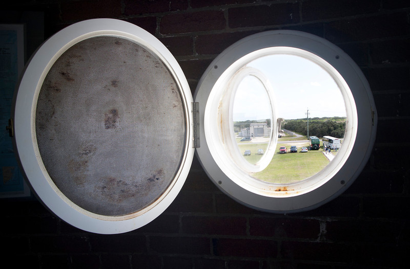 View out one of the portholes with the screen open of the tour buses arrival.