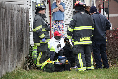 The driver of the car, in red ball cap, speaks with Sharon Yount and paramedics, while homeowner Gerald Anderson (center) looks on. photo by Ray Riedel