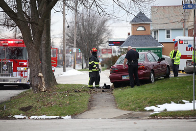 Firefighters insure against the risk of fire or explosion while a police officer investigates the single car accident on East Broad Street Christmas day. photo by Ray Riedel