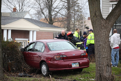 While police and firefighters investigate the crash, paramedics and neighbors look after the driver who was able to exit the car. photo by Ray Riedel