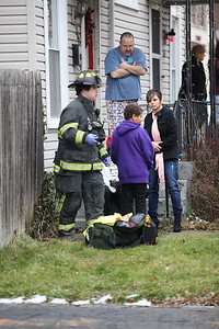 Gerald Anderson, top center, looks down at the driver on his porch steps while  Sharon Yount and her son Mykal Bowens (age 12) stand near the driver as paramedics administer care. photo by Ray Riedel