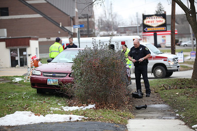 An officer investigates the car accident just past the intersection of Sumner and East Broad Street. photo by Ray Riedel