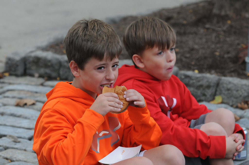. Josh and Karson Graber munch on hamburgers at the Carousel of Flavor Sunday. Photo by John Strickler/The Mercury