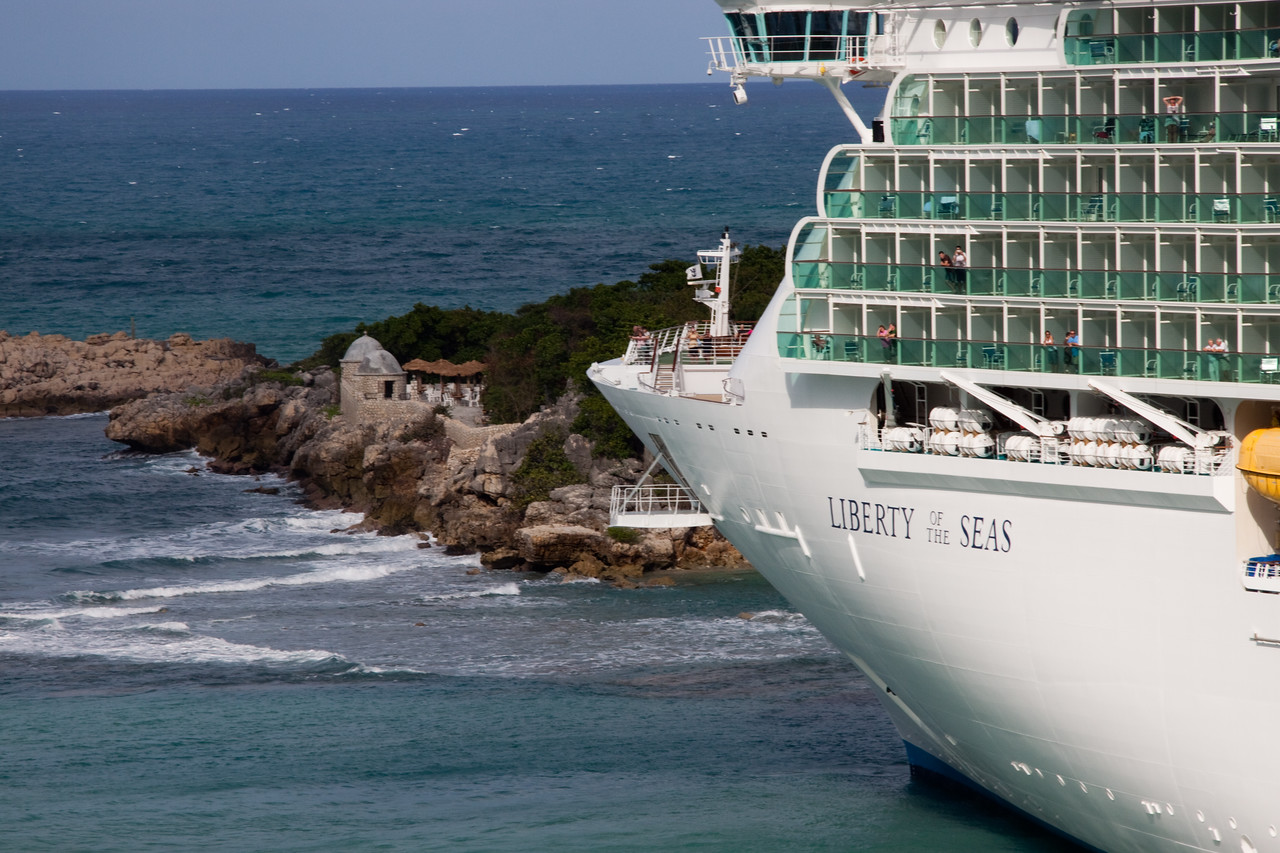 Liberty of the Seas moored at Labadi in a manner where you see the point and nose of the ship together.