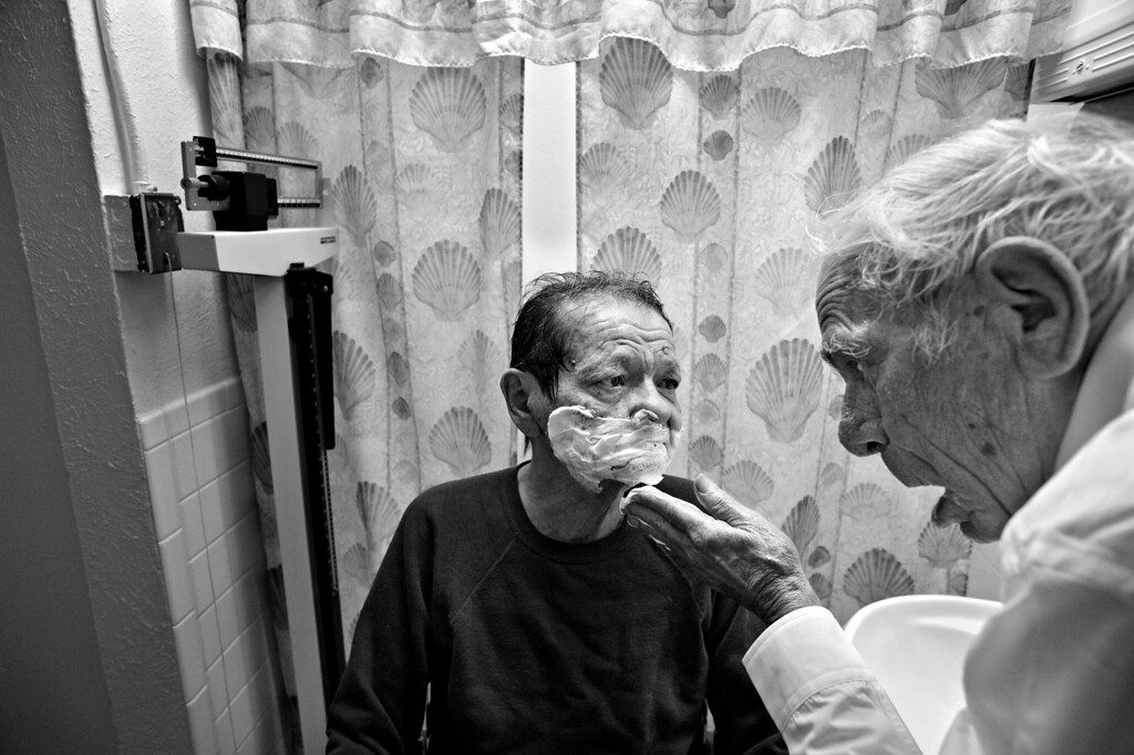 ". Cecil Bethea shaves the face of his partner, Carl Shepherd, during one of Cecil\'s many visits to The Spearly Center, where Carl lives, in Denver, Colo. Cecil bathes and shaves Carl\'s face every other day. ""As I remember in the old time wedding vows, there was a phrase in there, \'in sickness and in health,\'\"" Cecil says. \""Well this is certainly sickness. And if I didn\'t do it, who would... I\'m the only one he has.\"" (Photo By Craig F. Walker/The Denver Post)"