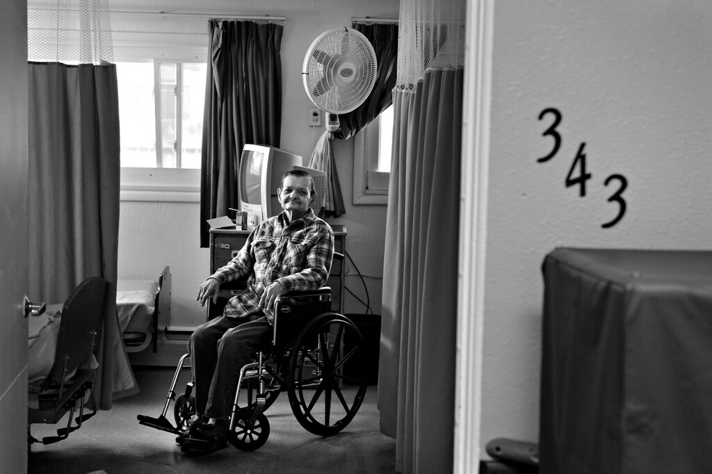 ". Carl watches from his room as his partner, Cecil, leaves the The Spearly Center. Cecil said it was incredibly difficult to leave when Carl was first admitted to the nursing home. ""That was terrible... when I would leave he would want to go home with me, and we would have to get the attendants to hold him,\"" Cecil said. \""That was hard, mighty hard.\"" (Photo By Craig F. Walker/The Denver Post)"