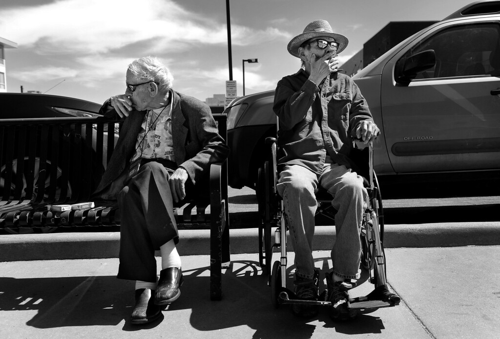 ". Conversation is scarce as Cecil and Carl smoke cigarettes near The Spearly Center before Carl returns him to his room. Carl, who was admitted to the nursing home over a year ago, suffers from dementia. ""You see, he\'s not Carl anymore,\"" Cecil said. \""He\'s almost like a little child. When I walk in to see him, the first thing he asks me is \'Can we go for a smoke?\'\"" Cecil said he sometimes feels like Carl\'s cigarette dispenser, which bothers him. \""I chatter like an irritated squirrel, and he just sits there. That\'s mighty hard to take.\"" (Photo By Craig F. Walker/The Denver Post)"