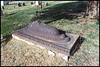 Side view of an unlabeled metal grave top in Lee's Summit City Cemetery, Lee's Summit, Missouri, north Highway 291.  Acorns, symbolizing potential, adorn the top.  Nov. 17, 2001
