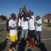 Winning team celebrates with their trophy at the Champion's League tournament at VPUU field in Harare Peace Park in Khayelitsha, April 2014.  (After the official Champs League pilot ended, 4 Champs League Coaches continued the league with former participants and other young men in the community.)