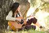Choice 5 of 18 / A woman plays the guitar under an oak tree.