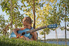 Choice 3 of 18 / Girl Playing Guitar in Grass by Water