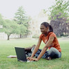Female college student using laptop computer outdoors