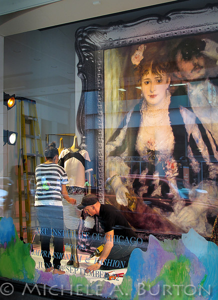 Renoir's model watches as Macy's window gets dressed