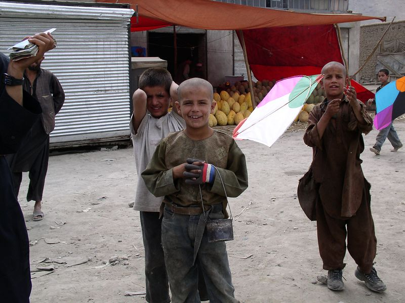 Childhood in Afghanistan. The bucket is to keep bad spirits away. The child on the right is the kite flyer.