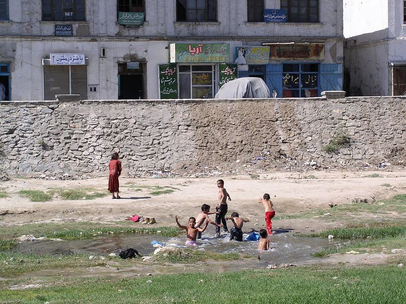 Kids will be kids. They are playing in the dry Kabul River bed where a small amount of rain water (+ solid waste) has collected. The river bisects the city similar to the Potomac and appears to have been the approximate depth of Potomac.