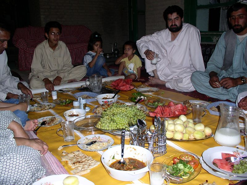 "My Afghani dinner at a local MD's house. The serious-looking man is the son-in-law, a surgeon working with Red Crescent. Afghanis ""look serious"" for pictures despite their otherwise congenial spirit !! It was a delicious dinner."