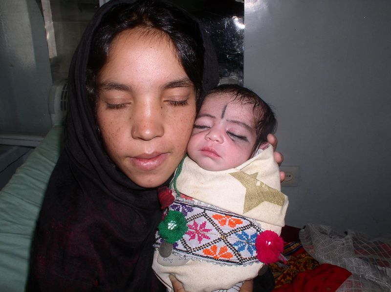 This is a mother from the Pashtun tribe. Her eyes are closed because she is demonstrating why they believe in using the coal to create eyeliner and eyebrows - for assure growth !